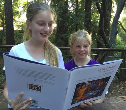 2 Girls reading the book Dende Maro