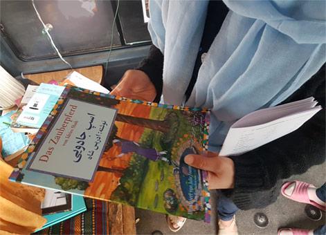Girl looking at the German-Dari edition of The Magic Horse